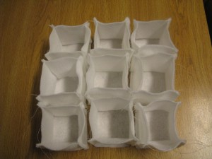 "Nine white 3"" x 3"" x 3"" felt boxes"
